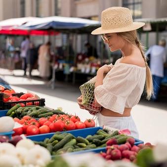 Вид сбоку женщина, использующая органический мешок для овощей