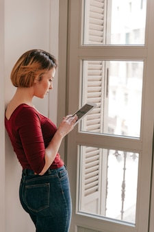 Side view woman using tablet near window