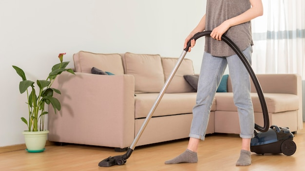 Side view of woman using vacuum cleaner in room