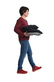 Side view of a woman walking and holding a pile of clean clothes on white background