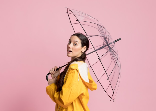 Side view woman walking with an opened umbrella