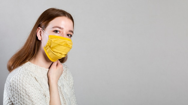 Side view of woman wearing a medical mask with copy space