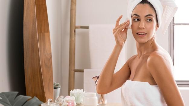 Donna di vista laterale che indossa gli asciugamani e usando la crema
