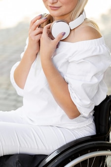 Vista laterale della donna in sedia a rotelle in città con le cuffie