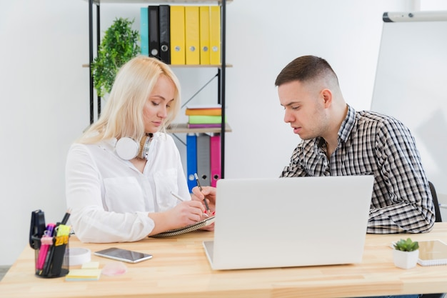 Side view of woman in wheelchair and colleague conversing at desk