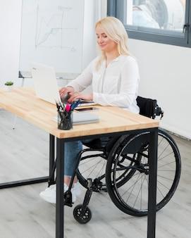 Vista laterale della donna in sedia a rotelle al funzionamento dello scrittorio