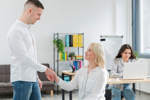 Side view of woman in wheelchair shaking hand with coworker