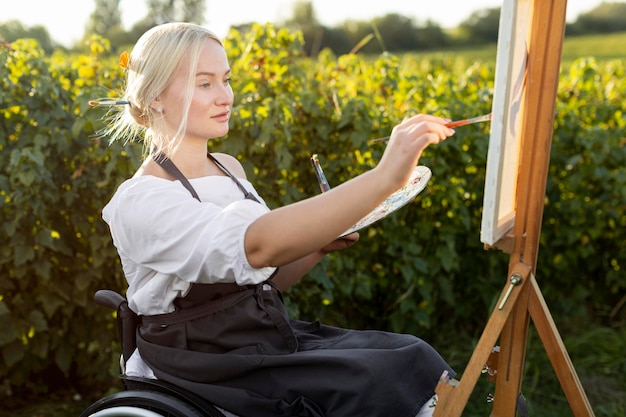Side view of woman in wheelchair with canvas and palette