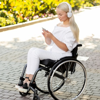 Vista laterale della donna in sedia a rotelle con cuffie e smartphone