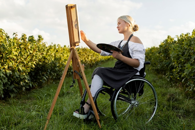 Side view of woman in wheelchair with palette and canvas