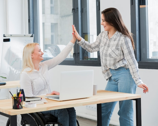 Side view of woman in wheelchair at work high-fiving her colleague