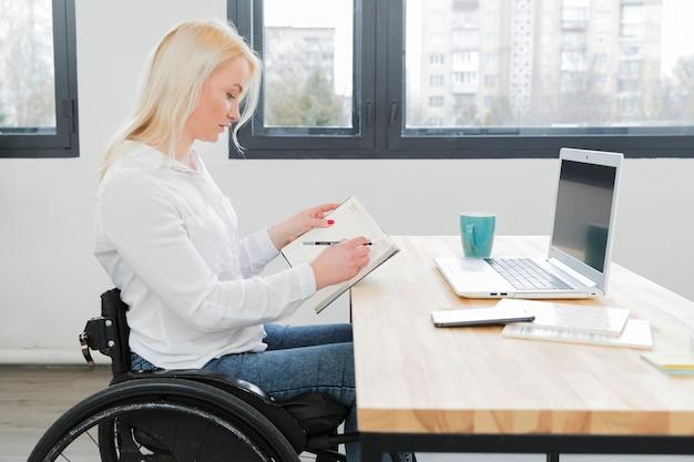 Vista laterale della donna in sedia a rotelle che lavora allo scrittorio