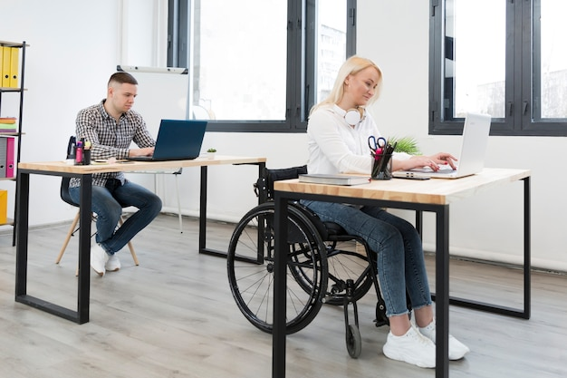 Side view of woman in wheelchair working form her desk