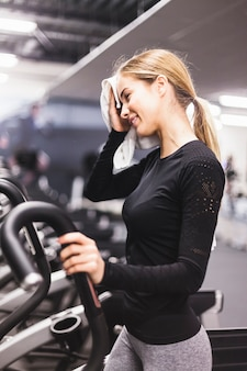 Side view of a woman wiping sweat while exercising in gym