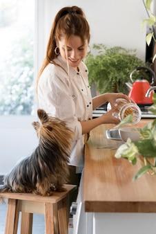 側面図女性ウィット犬キッチンの横に