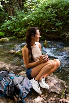 Side view of woman with backpack resting while exploring nature