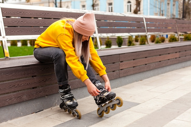 Side view of woman with beanie adjusting roller blades