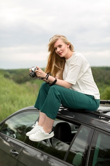 Side view of woman with camera on top of car
