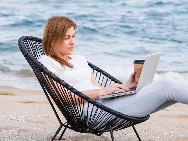 Side view of woman with coffee working in beach chair on laptop