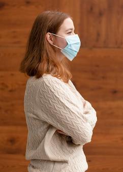 Vista laterale della donna con le braccia incrociate che indossa una maschera medica