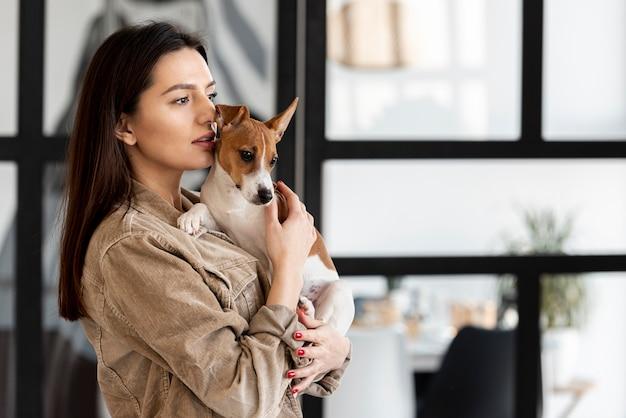 Vista laterale della donna con cane carino tra le braccia