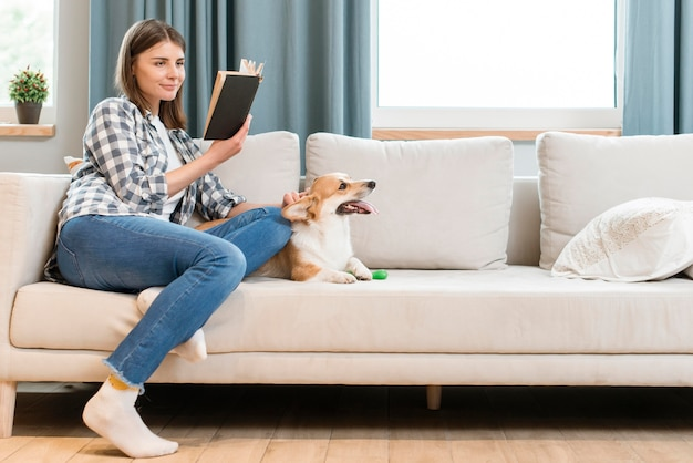 Side view of woman with dog reading a book on the couch