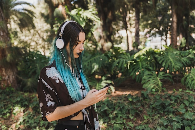 Side view of woman with dyed hair listening music on headphone using smart phone