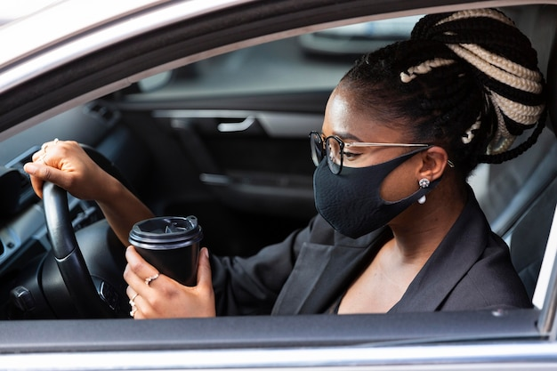 Side view of woman with face mask having coffee inside her car