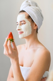 Side view of woman with face mask holding strawberry