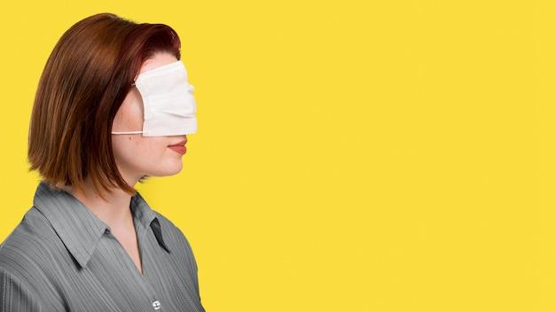 Вид сбоку женщина с маской на глазах, стоящая рядом с освещающей стеной