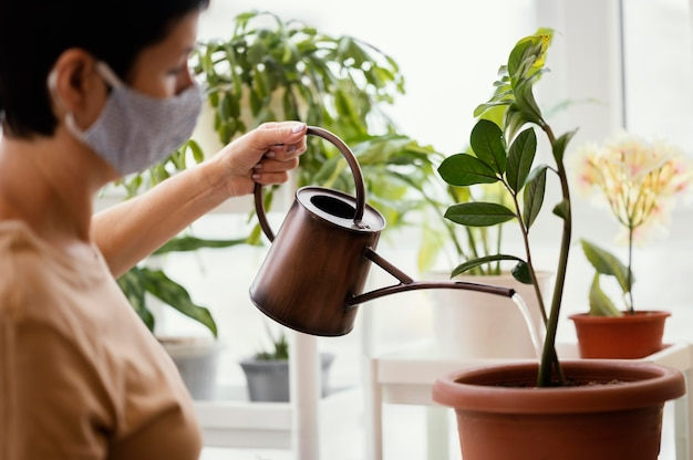 Side view of woman with face mask using watering can for indoor plant