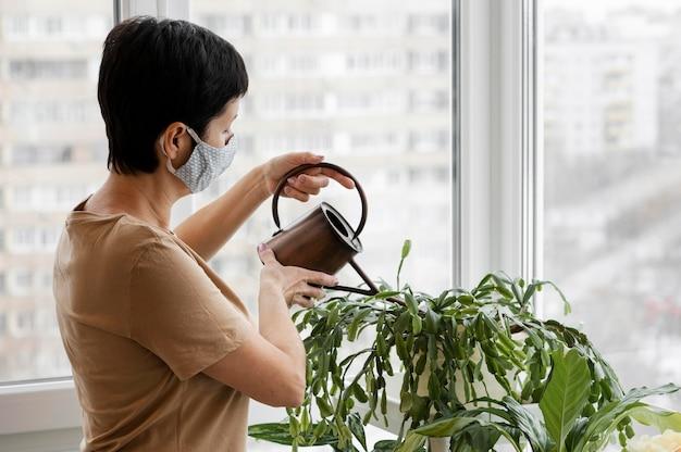 Vista laterale della donna con la maschera per il viso innaffiare piante da interni
