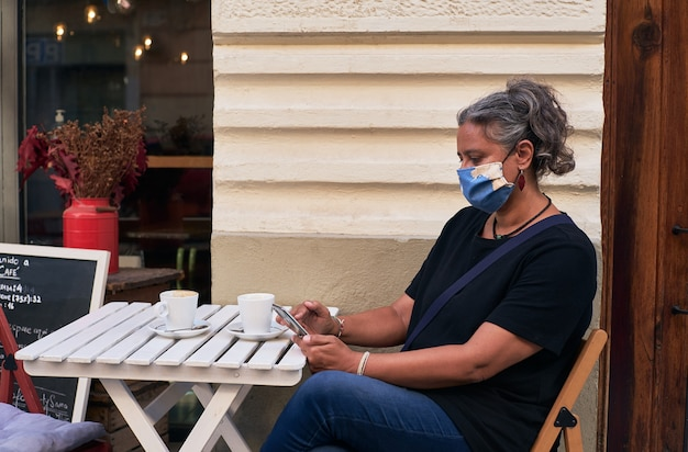 Side view of a woman with a face mask while using her phone on the outdoor table of a cafe