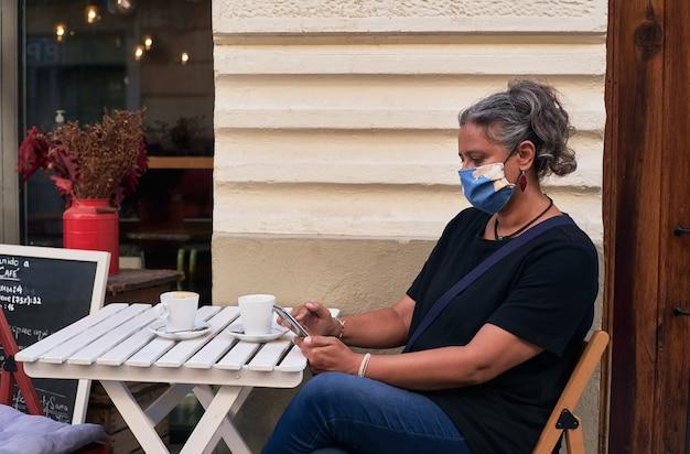 Vista laterale di una donna con una maschera facciale mentre utilizza il suo telefono sul tavolo all'aperto di un caffè