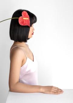 머리에 꽃을 가진 측면보기 여자