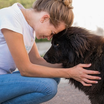 Vista laterale della donna con soffice cane nero all'aperto