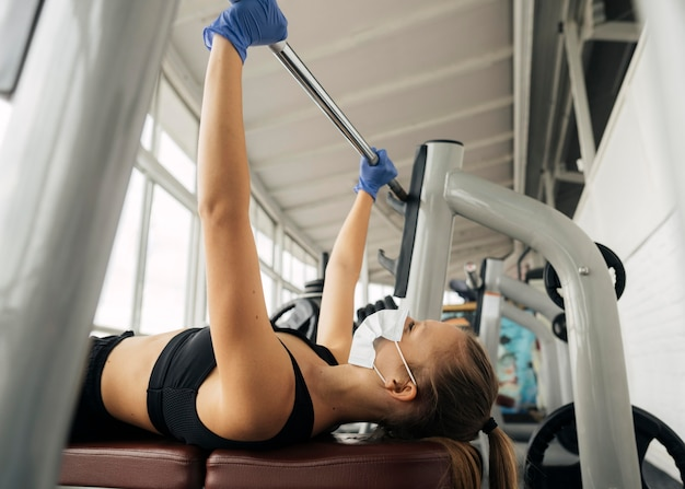 Side view of woman with gloves working out at the gym