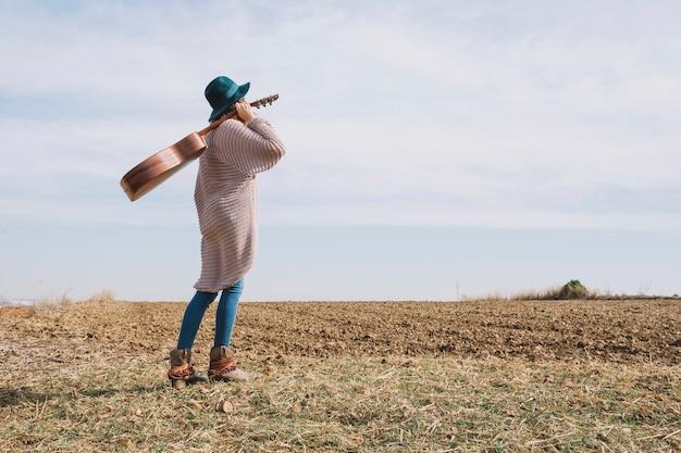 フィールドでギターを持つサイドビューの女性