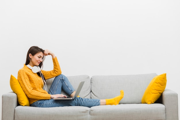 Side view of woman with headphones sitting on sofa with laptop