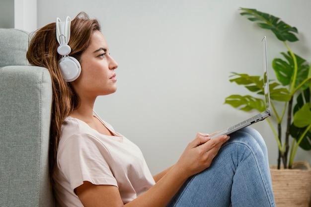 Donna di vista laterale con le cuffie utilizzando il computer portatile