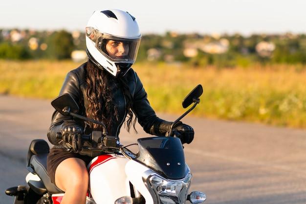 Vista laterale della donna con il casco in sella a una moto