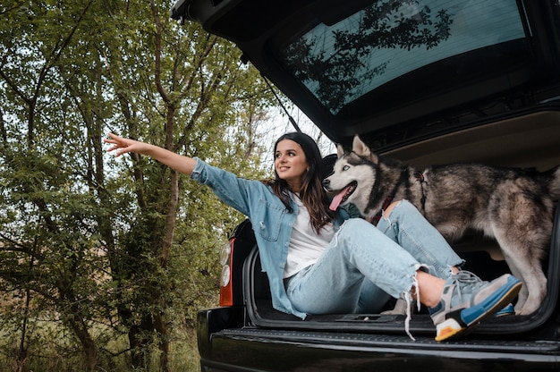 Side view of woman with her cute husky traveling by car