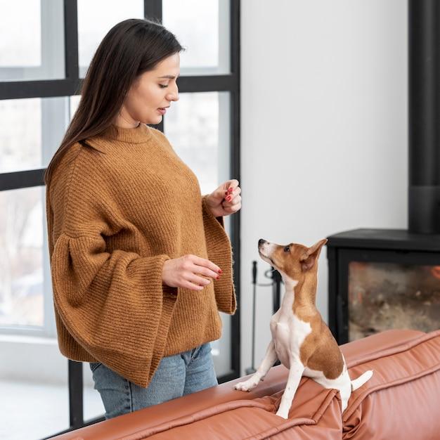 Vista laterale della donna con il suo cane sul divano
