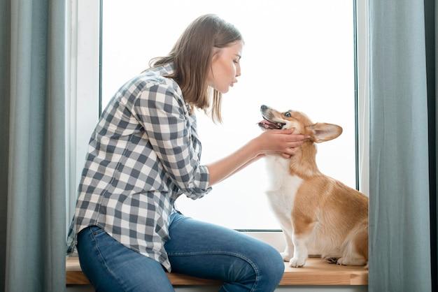 Vista laterale della donna con il suo cane davanti alla finestra