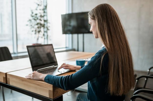 Vista laterale della donna con il computer portatile che prepara per una riunione