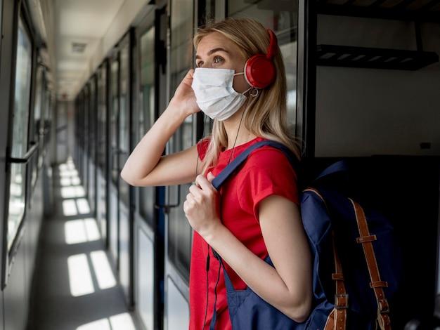 マスクと電車の中でヘッドフォンを持つサイドビュー女性