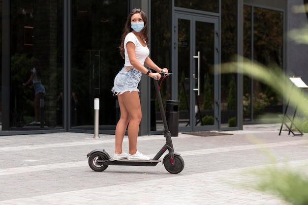 Side view of woman with mask riding an electric scooter