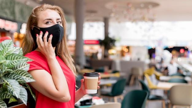 携帯電話で話しているマスクを持つサイドビュー女性