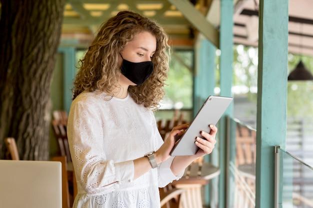 タブレットを使用してマスクを持つサイドビュー女性