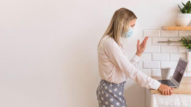 Вид сбоку женщина с маской, работающей дома